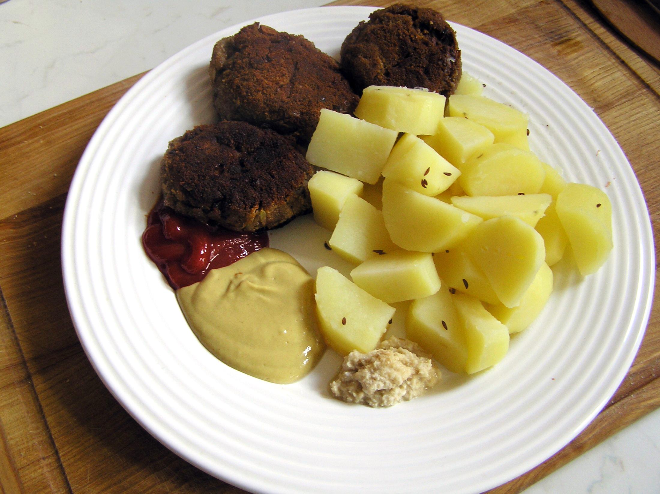 Recept Smažené karbanátky - Hotové karbanátky s vařenými brambory, trochou hořčice, kečupu a křenu.