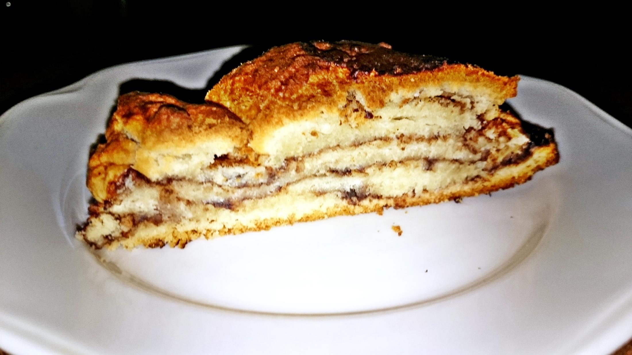 Recept Pletený kysnutý jogurtový koláč s kakaom - Upečeme a vychladnutý koláč pokrájíme na porce