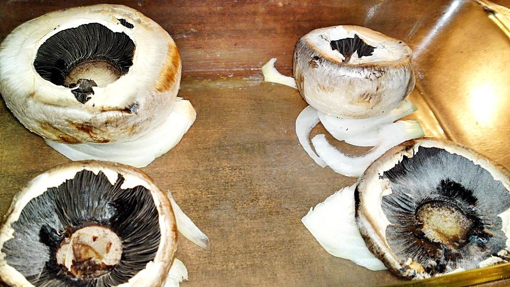 Recept Pečené šampiňóny plnené syrovo - smotanovou náplňou - Položíme kloboučky hub na měsíčky cibule.