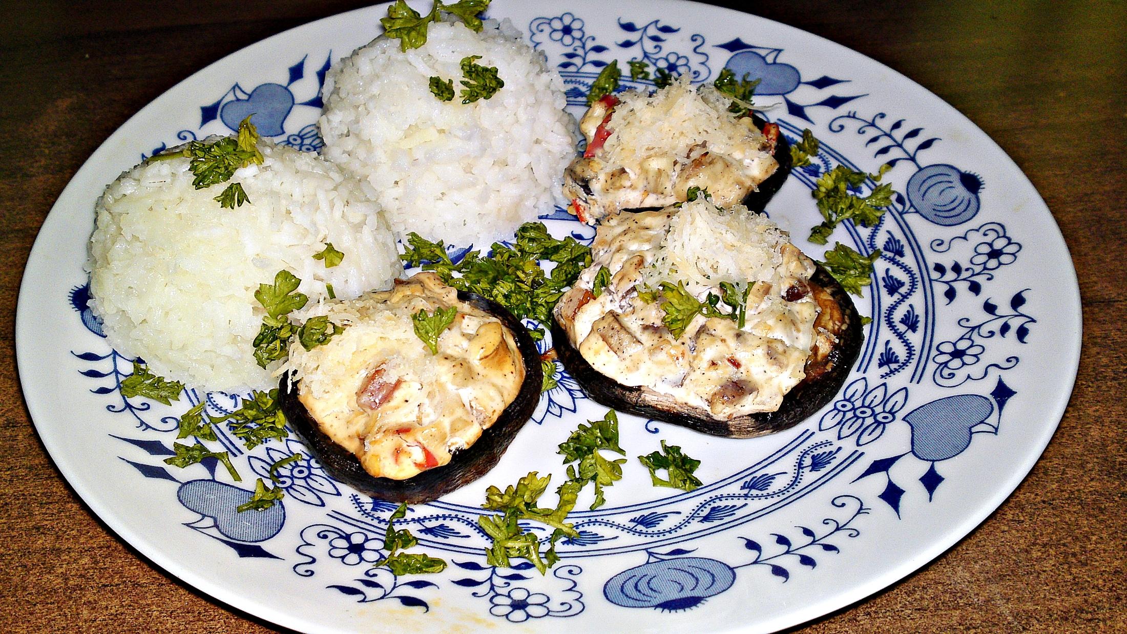 Recept Pečené šampiňóny plnené syrovo - smotanovou náplňou - Servírujeme horké s dušenou rýží, kloboučky hub posypeme zbylým sýrem a ozdobíme petrželovou natí.