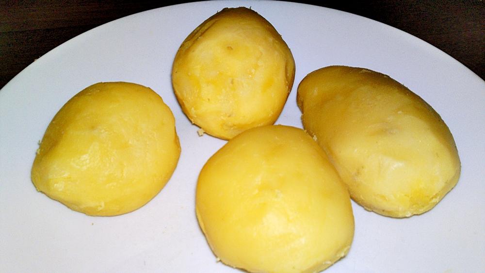 Recept Pečené kačacie stehná s krájanými zemiakmi na cibuľke a na rasci - Oloupeme ve slupce uvařené brambory.