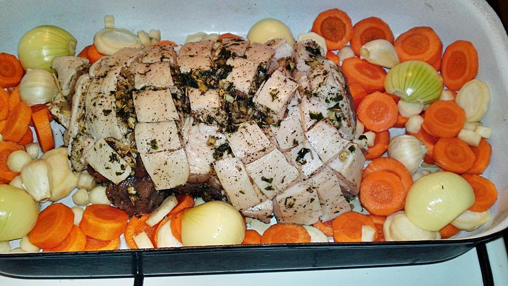 Recept Porchetta - bůčková roláda - Vybereme z chladničky, na spodek pekáče položíme pokrájenou mrkev, petržel, cibuli a půl paličky stroužků česneku v slupce.