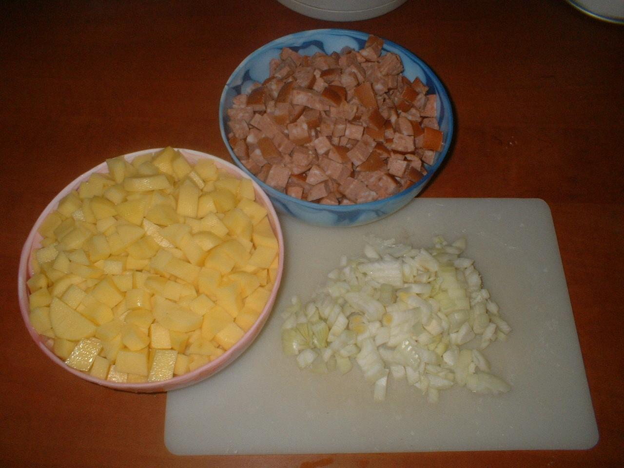 Nakrájíme brambory, buřty a cibulku.